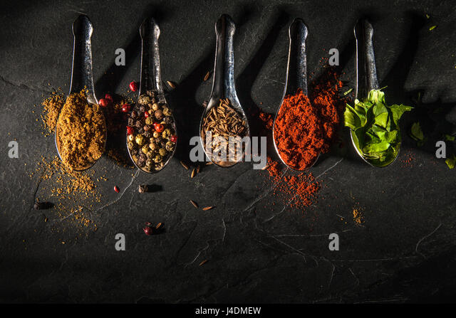 Five Spice spoons on slate background with shadow - Stock Image