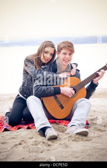 Teen couple on the beach - Stock Image