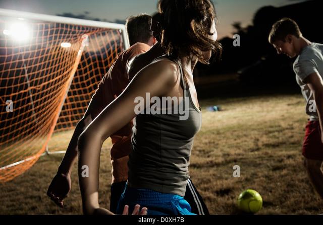 Friends playing soccer at night - Stock-Bilder