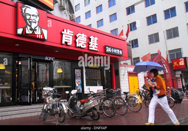 Beijing China Xicheng District Guang An Men Nei Da Jie Guanganmen Inner Street Asian woman umbrella KFC fast food - Stock Image