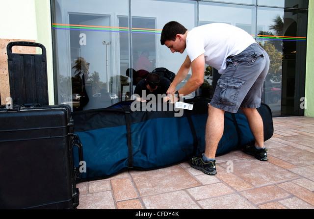 Two male surfers open up their board bags while at Manzanillo International Airport in Colima, Mexico. - Stock Image