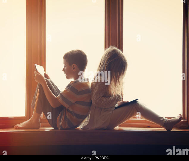 Two children are sitting by the window at home playing on their technology tablets with games and apps for a entertainment - Stock Image