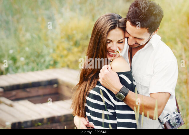 happy romantic couple in love and having fun with daisy at the lake outdoor in summer day, beauty of nature, harmony - Stock-Bilder