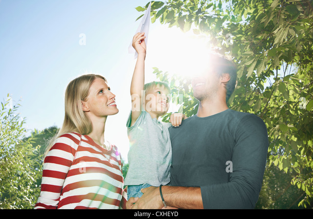 Germany, Cologne, Family playing with paper plane, smiling - Stock Image