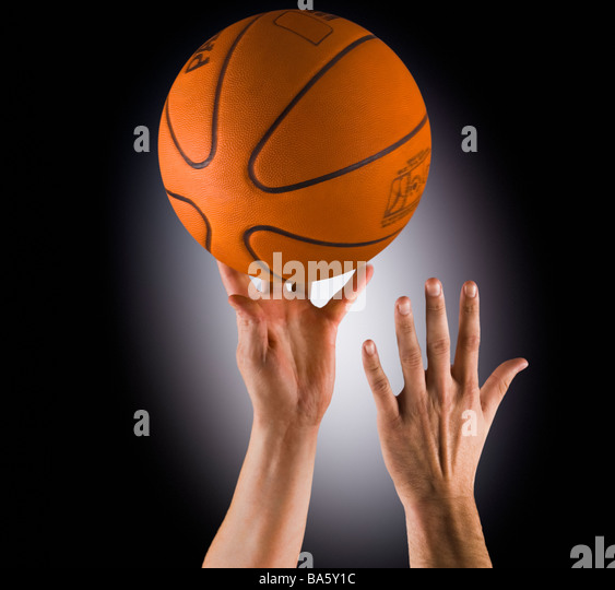 Two hands going for the basketball, tip off/ jump ball - Stock Image