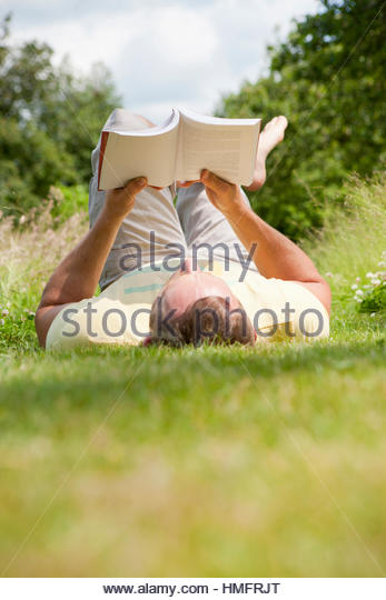 Man reading book relaxing in sunny summer rural grass - Stock-Bilder