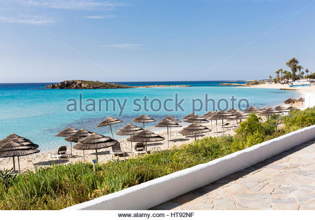 Beach umbrellas on Nissi Beach at the Nissi Beach Resort with stone walkway in Agia Napa, Cyprus - Stock-Bilder