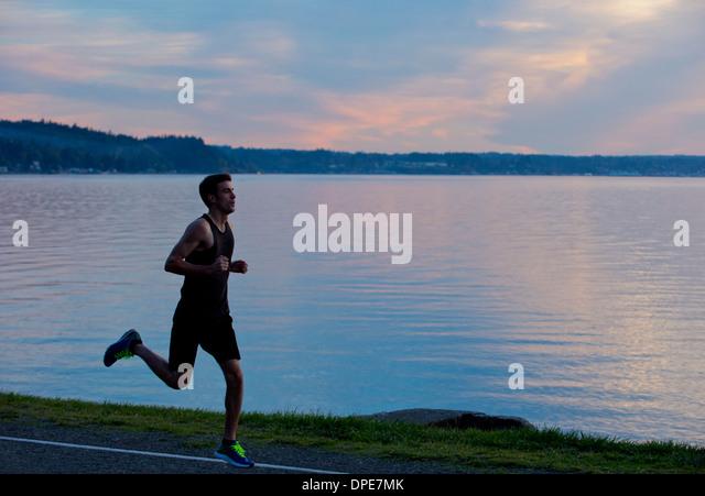 Jogger running past lake - Stock-Bilder