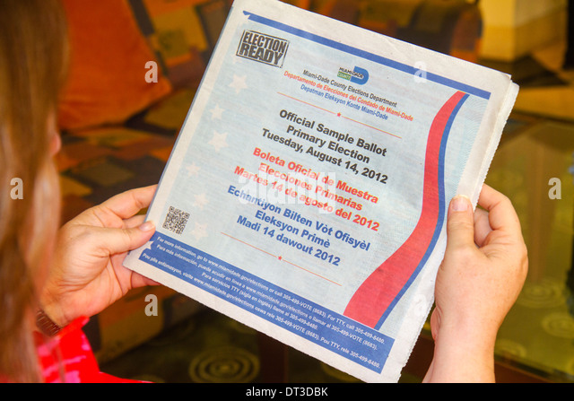 Miami Beach Florida woman reading municipal ballot information sample English Spanish Creole language elections - Stock Image