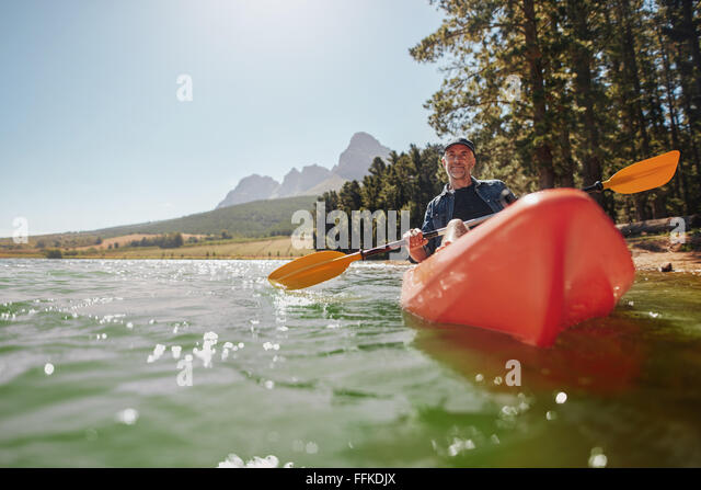 Rear view of a senior man canoeing in a lake on a sunny day. Senior man paddling kayak. - Stock Image