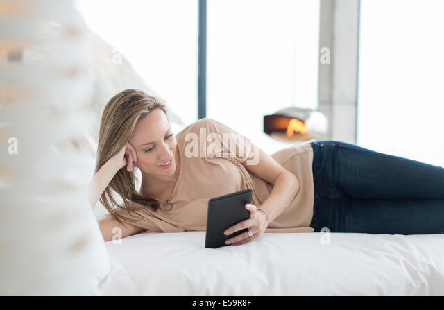 Woman using digital tablet on bed - Stock Image
