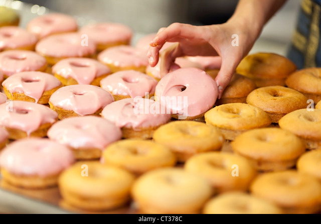 A woman adds a pink glaze while baking doughnuts at Tandmen Doughnuts, a small boutique bakery in Missoula, Montana. - Stock Image