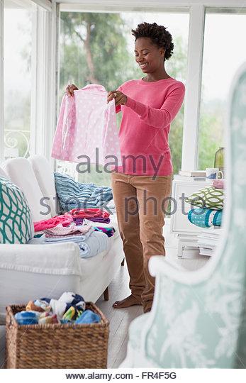 mid adult woman folding laundry in sunroom - Stock-Bilder