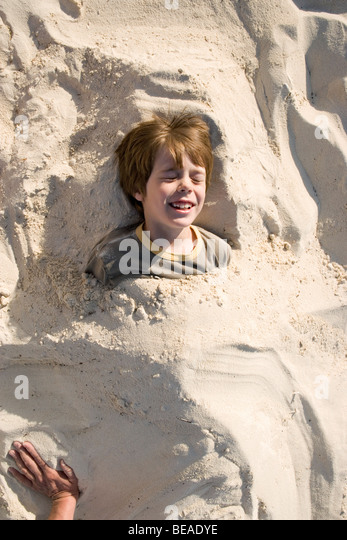 A young boy buried in sand, Cable Beach, Nassau, Bahamas, Caribbean - Stock-Bilder
