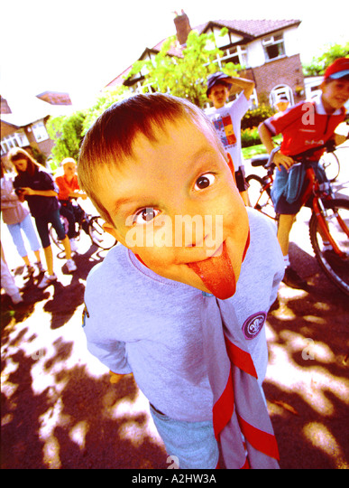 Boy age 6-10 pulling tongues. - Stock Image
