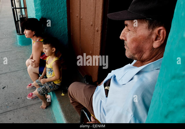 A man watches over his family on the doorstep to their home in the 500 year old city of Sancti Spiritus, Cuba. Cubans - Stock-Bilder
