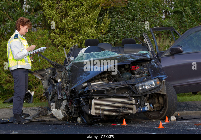 A police crash investigator at the scene of a collision between a bus and a car - Stock Image