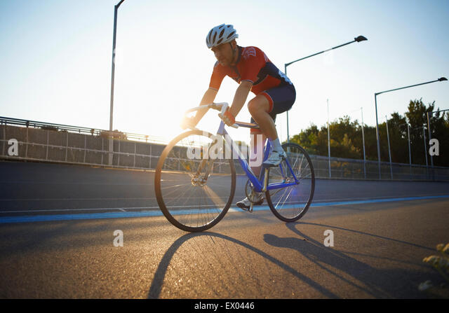 Male cyclist cycling on track at velodrome, outdoors - Stock Image
