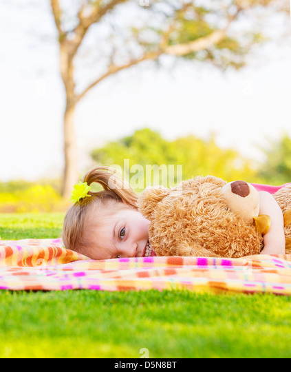 Adorable child resting on backyard in spring time, baby girl laying down on green field with teddy bear, having - Stock Image