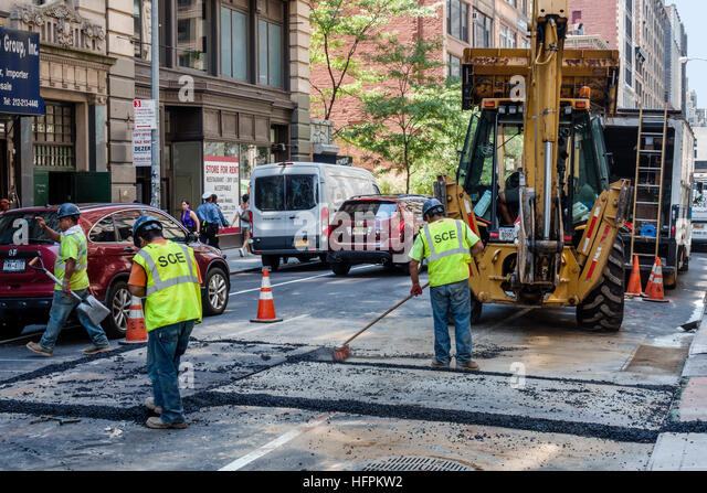 Manhattan New York City NYC NY NoMad DOT road work street construction pavement repair man worker laborer job repaving - Stock Image