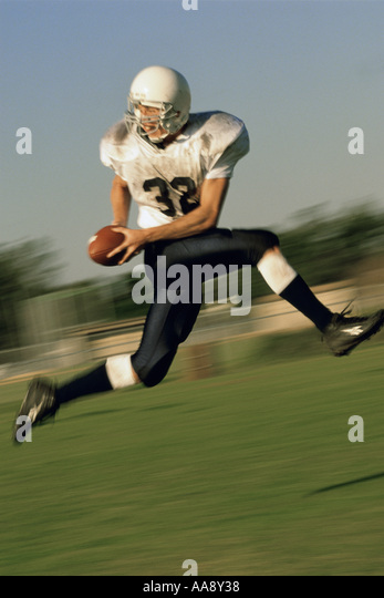 American football player running on a field - Stock Image