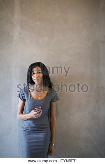 Portrait confident businesswoman holding cell phone gray background - Stock Image