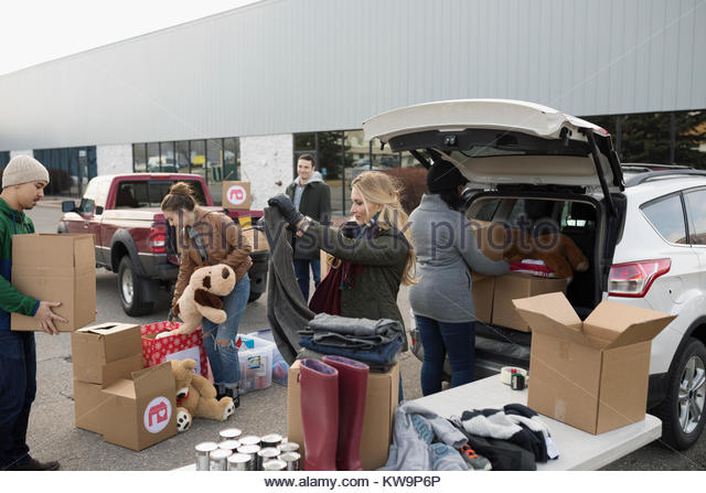 Young adult volunteers sorting and loading donations in parking lot - Stock Image