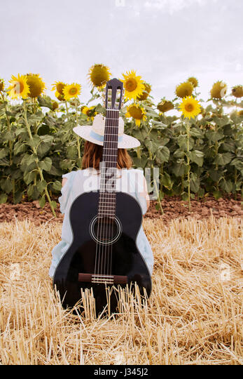 Young woman with her guitar in a field of sunflowers - Stock Image