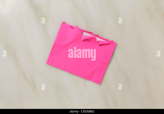 A used and slightly torn open postal envelope on a marble surface Bright pink colored envelope - Stock Image