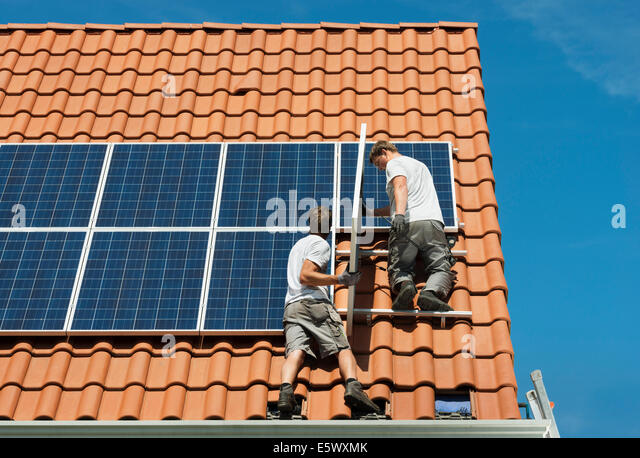 Workers installing solar panels on roof framework of new home, Netherlands - Stock Image