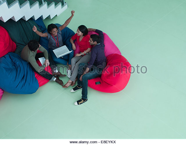 Excited business people with arms raised sitting in bean bag chairs and looking at laptop - Stock-Bilder