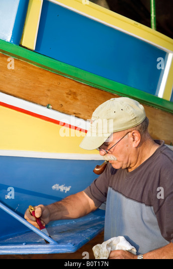Man repainting a Luzzu, eye painted on the front to protect the fishermen when they are out at sea. Traditional - Stock Image
