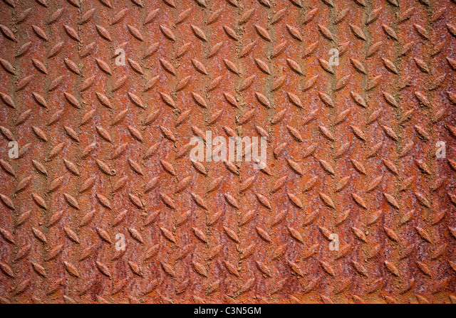 Photography shows a rusty metall background with diamond pattern. - Stock Image