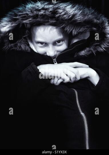 Young girl snug and warm in zip up coat with furry hood - Stock Image