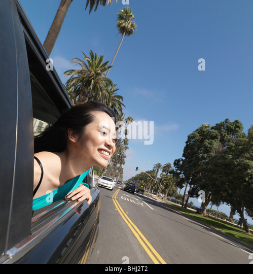 Young woman leaning out of car window - Stock Image