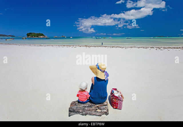young mother and her adorable daughter enjoying a day at tropical beach - Stock Image