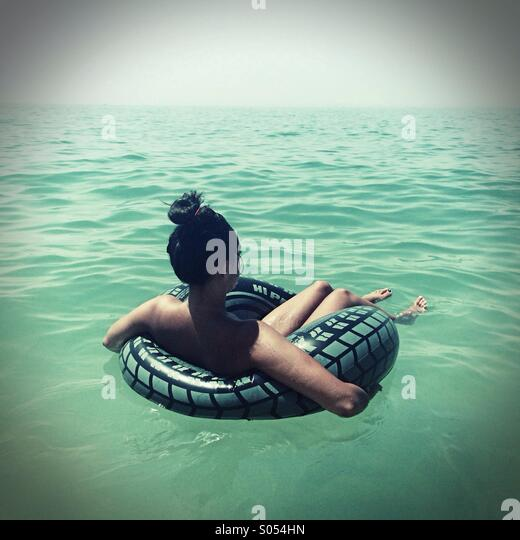 Young woman floating on a rubber ring in the Atlantic Ocean , Algarve, Portugal - Stock Image