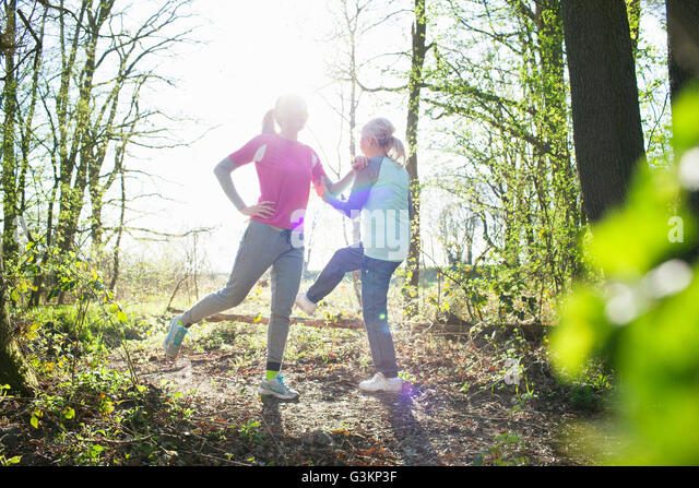 Women in forest face to face legs raised stretching - Stock Image