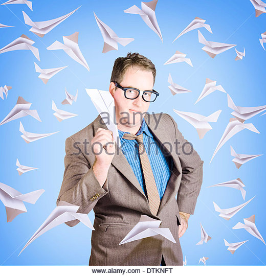 Business man flying paper aircraft in various directions in an international business travel concept - Stock Image