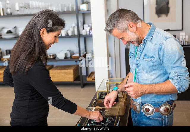 Man and woman examining jewelry in store - Stock-Bilder