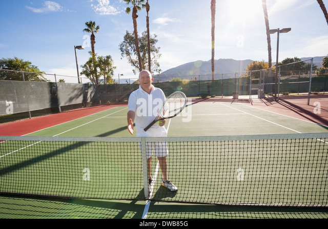 Portrait of senior tennis player offering handshake on court - Stock Image