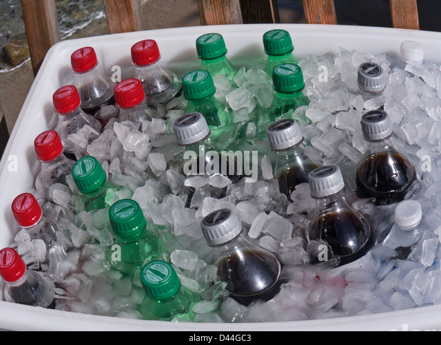 Plastic screw cap Cola soft drink bottles on ice for sale outdoors by street vendor on a sunny day - Stock Image