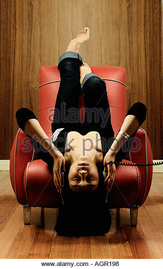 Woman sitting upside down listening to music - Stock Image