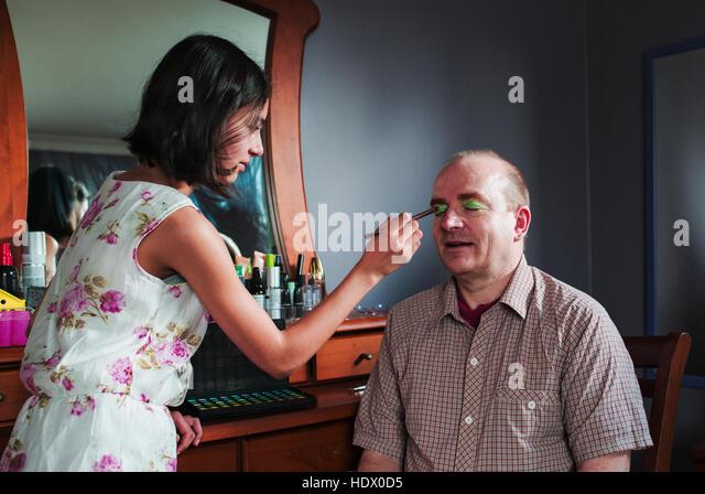 Girl applying makeup to eyes of father - Stock Image