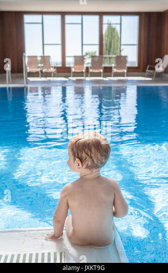Cute little baby boy sitting at the edge of pool. He is  putting his legs into the water - Stock Image