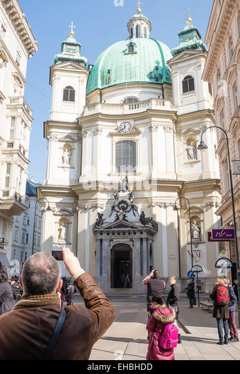 Petersplatz, Vienna. A tourist taking a photo of Kirche St. Peter with his mobile phone - Stock Image