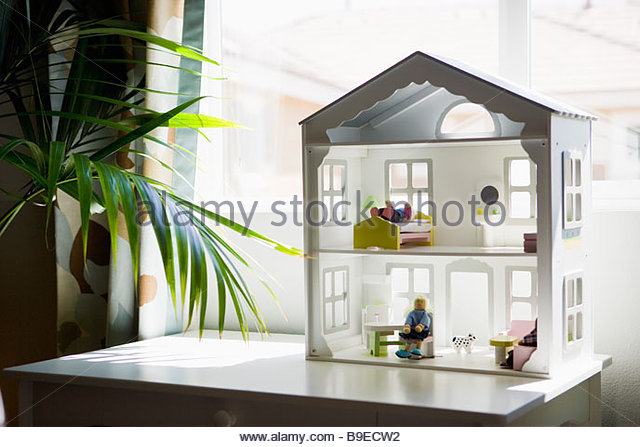 Childs doll house on trunk in front of windows - Stock Image