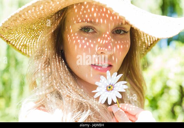 MODEL RELEASED. Young woman wearing sunhat holding daisy. - Stock-Bilder