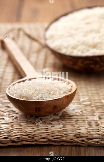 Basmati rice in wooden spoon on straw background - Stock Image