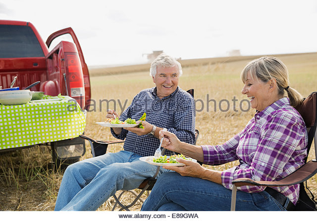 Senior couple enjoying lunch in crop field - Stock Image